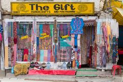 Front view of Tibetan shop clothes and souvenirs in Leh, Ladakh, India. LEH, INDIA - JUNE 29, 2015 : Front view of Tibetan shop clothes and souvenirs outside the stock images