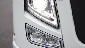 Front view of a truck headlight closeup in rainy weather, camera paning. HD stock video