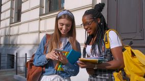 Front view of two beautiful students of African and European descent, standing together. Women study together in a. Luxurious international school and maintain stock video footage
