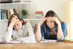 Two fatigued students studying hard. Front view of two fatigued students studying hard at home royalty free stock photography