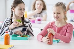 Front view of two junior girls in a school cafeteria during lunch break. One holding a wholewheat sandwich, the other opening a b