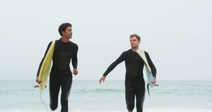 Front view of two male surfers running together with surfboard on the beach 4k. Front view of two male surfers running together with surfboard on the beach. They stock footage