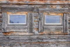 Two windows on a weathered and aged log cabin. Front view of two windows on a weathered and aged log cabin royalty free stock photos