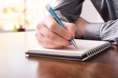 Front View Of un uomo nella scrittura della camicia di affari in un blocco note in bianco con un biro immagini stock