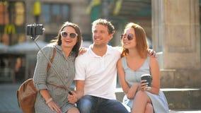 Front View van Drie Gelukkige Vrienden die Selfie nemen in openlucht Gebruikend Smartphone op het Stadsvierkant tijdens Sunny Sum stock videobeelden