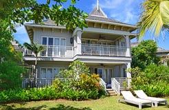Front View van grote die de bungalowtoevlucht van A met sundeckstoelen in voorzijde door groene bomen en installaties wordt omrin Royalty-vrije Stock Afbeelding