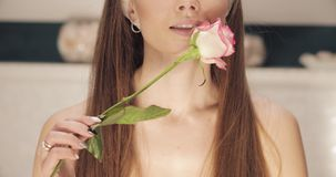 Front view view of woman touching soft skin with rose. Front view view of attractive young woman touching soft skin with pink rose at home. Perfect lady caring stock video