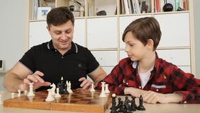 Front view of warm and kindly atmosphere of the intelligent process of playing chess between the son and his father slow stock video
