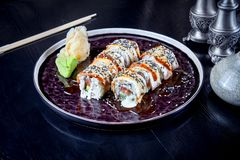 Front view on warm roll with tuna, eel and cream. Suchi. japanese food style. Seafood. Healthy, balanced, dieting meal. sushi. Rolls set on dark plate. Copy stock photo
