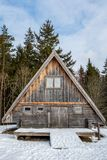 Weathered and aged log cabin surrounded by trees and snow. Front view of a weathered and aged log cabin surrounded by trees and snow, vertical composition royalty free stock image