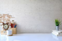 Front view of white desk with coffee mug and house plant. workspace and copy space. White desk table with copy space, supplies and coffee mug. Front view royalty free stock photo