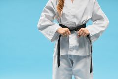 Front view of kimono on little fighter keeping black belt stock photography