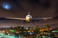 Front view of white passenger plane in the sky. White passenger plane in flight during the night. Aircraft flying in moonlight over the night city. Airplane Stock Photos