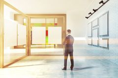Front view of white and wooden poster gallery man. Front view of a white wall poster gallery with large windows, a white floor and two vertical mock up posters Stock Photography