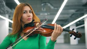 Front view of a woman with bronze hair playing the violin stock video