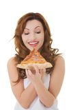 Front view of a woman eating pizza Royalty Free Stock Photography