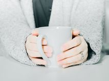 Front view from woman hand with cloth hold the white hot coffee. Cup from hand warming and drink on morning time with soft focus background Stock Image