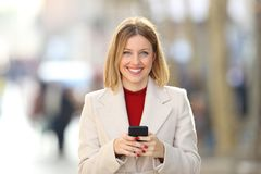 Front view of a woman holding a phone looking at you. Front view portrait of a woman holding a smart phone looking at you on the street in winter Royalty Free Stock Images
