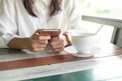 Front view. woman playing mobile phone while take a break in morning time. front of her having coffee cup putting on wooden table. Front view. young woman royalty free stock images