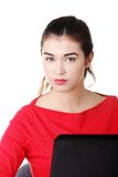 Front view woman sitting at the desk with laptop.  Royalty Free Stock Photo