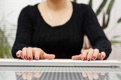 Front view woman is typing on white keyboard at home stock photo