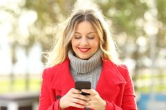 Front view of a woman using a smart phone in winter. Front view portrait of a woman using a smart phone outdoors in a park in winter Royalty Free Stock Images