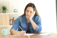 Worried woman writing notes or a letter. Front view of a worried woman writing notes or a letter at home stock image