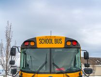Front view of a yellow school bus with homes and cloudy sky in the background. Several side mirros and signal lights can be seen at the front of the school bus royalty free stock images