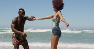 Couple dancing together on beach in the sunshine 4k