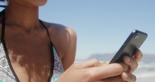Front view of young African american woman in bikini using mobile phone on the beach 4k. Front view of young African american woman in bikini using mobile phone stock footage