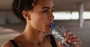 Front view of young African American woman drinking water in the city 4k stock video