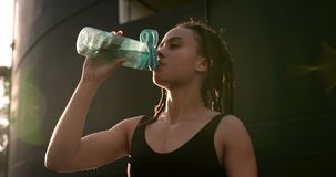 Front view of young African American woman drinking water in the city 4k stock video footage