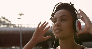 Front view of young African American woman listening music on headphones in the city 4k stock video footage