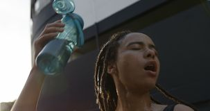 Front view of young African American woman pouring water on her head in the city 4k stock footage
