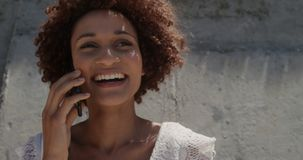 Front view of young African american woman talking on mobile phone at beach in the sunshine 4k stock footage