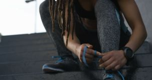 Front view of young African American woman tying shoelaces in the city 4k stock video