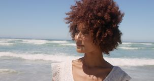Front view of young African american woman walking on beach in the sunshine 4k stock video footage