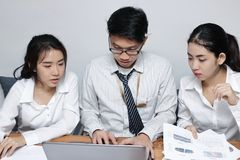 Front view of young Asian business people working together on a laptop computer at office. Teamwork brainstroming concept. Selecti. Ve focus and shallow depth of Stock Images
