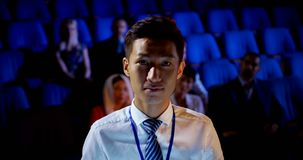 Young Asian businessman attending business seminar in auditorium 4k. Front view of young Asian businessman attending business seminar in auditorium. He is stock video footage