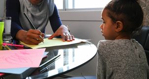 Young mother helping her daughter with homework on table 4k. Front view of a young Asian mother wearing a hijab and helping her daughter with the homework by