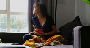 Front view of young asian woman having coffee in living room at home 4k
