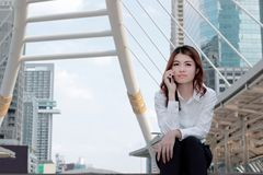 Front view of young attractive Asian business woman talking on mobile smart phone in the city building with copy space background. Front view of young stock images