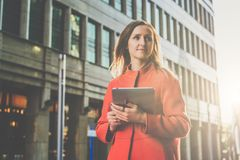 Front view. Young attractive woman in orange coat standing on city street holding tablet computer.Girl student Royalty Free Stock Photo
