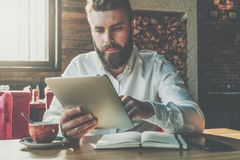 Front view.Young bearded businessman sits in cafe at table,uses digital tablet.On desk is notebook,cup of coffee. Stock Images