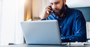 Front view.Bearded businessman is sitting at table in front of computer, talking on cell phone. Freelancer works at home. Front view. Young bearded businessman Stock Photo