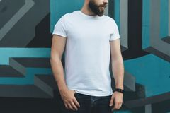 Front view. Young bearded hipster man dressed in white t-shirt is stands against wall with graffiti. Mock up. Royalty Free Stock Photos