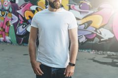 Front view. Young bearded hipster man dressed in white t-shirt is stands against wall with graffiti. Mock up.