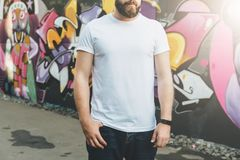 Front view. Young bearded hipster man dressed in white t-shirt is stands against wall with graffiti. Mock up. Stock Photography