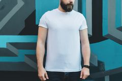 Front view. Young bearded hipster man dressed in white t-shirt is stands outdoor against wall with graffiti. Mock up. Stock Image