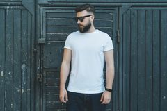Front view. Young bearded hipster man dressed in white t-shirt and sunglasses is stands against dark wood wall.